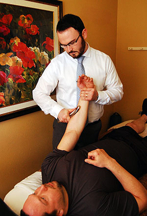 Chiropractor performing IASTM at his clinic in Portland, Oregon